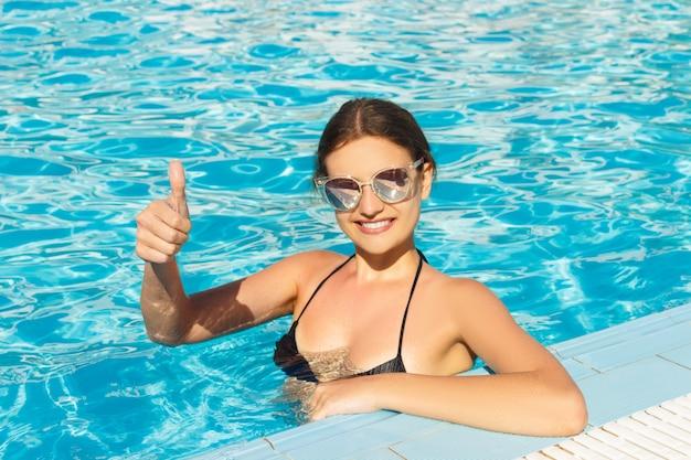 Счастливое лицо девушки показывает палец вверх в бассейне Premium Фотографии