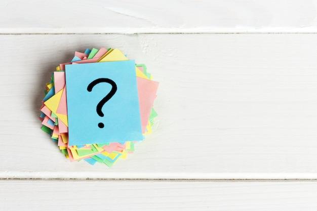 カラフルなクエスチョンマークがリマインダーチケットを書いた質問やビジネスの概念 Premium写真