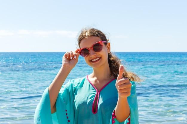 晴れた日に親指をあきらめてビーチで若い女性 Premium写真