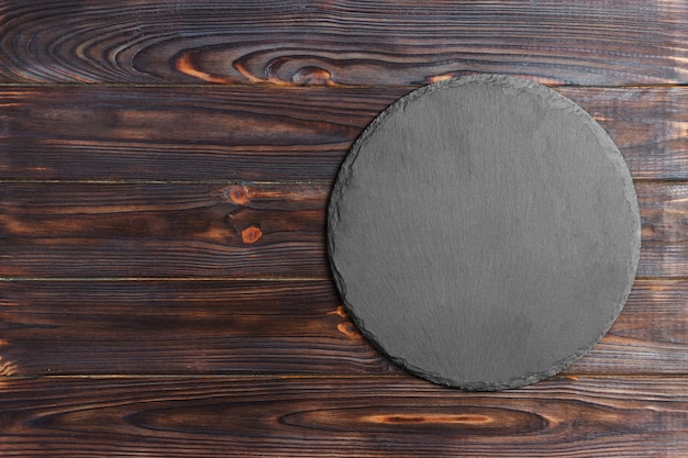 丸い天然スレート板。ダークグレーのスレートは木の表面に立っています。 Premium写真
