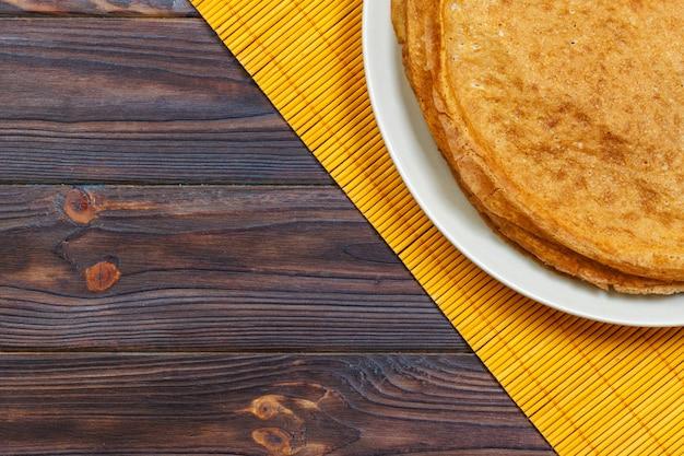 ロシアのパンケーキ週トップビューの伝統的なケフィアバターミルクパンケーキのスタック Premium写真