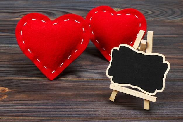 赤いハートの木製の背景に黒板。コピースペース Premium写真