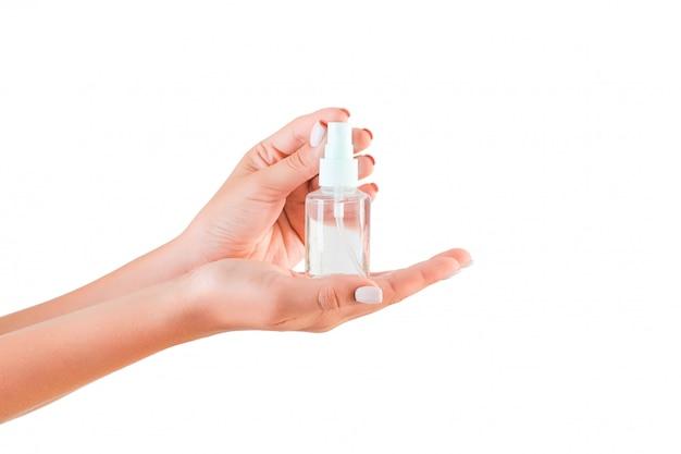 分離されたローションのクリームボトルを持っている女性の手 Premium写真