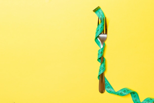フォークは黄色の測定テープに包まれています Premium写真