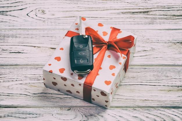 赤いハート、車のキー、ギフトボックスと休日のプレゼント Premium写真