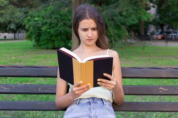 Потрясенная и удивленная женщина держит книгу и недовольна взглядом Premium Фотографии