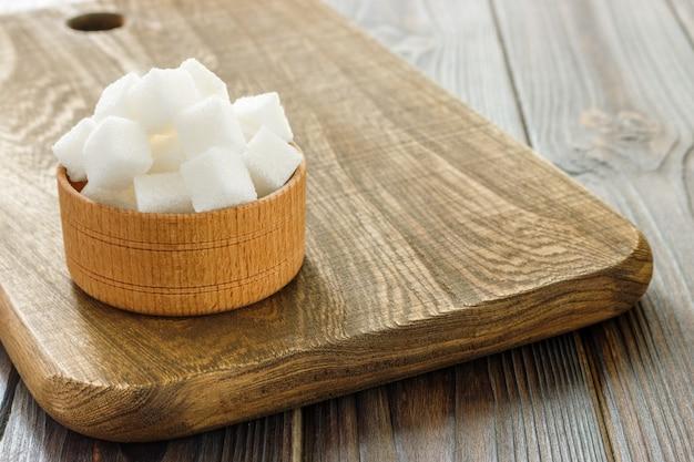 木製のテーブルの上にボウルに砂糖キューブ。ボウルに白砂糖キューブ Premium写真
