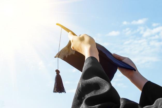 大学院生の開始日に彼女の手でキャップを祝う Premium写真