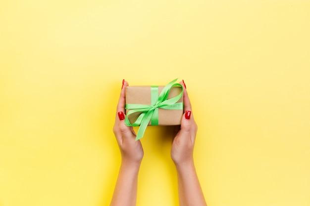 女性の手は赤いリボンと紙で包まれたバレンタインを与えます。 Premium写真
