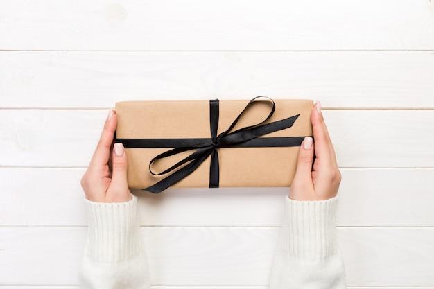 女性の手は、黒いリボンと紙で包まれたバレンタインや他の休日の手作りプレゼントを与えます。 Premium写真