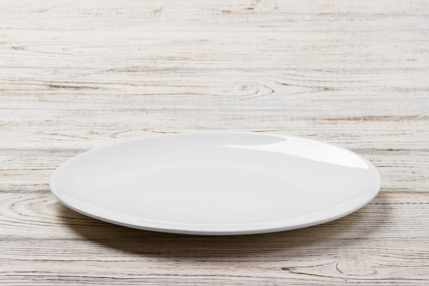 Белая круглая пластина на белом фоне деревянный стол. перспективный вид Premium Фотографии