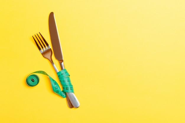 黄色の背景に巻尺で包まれたフォークとナイフの平面図です。健康的な食事とダイエットのコンセプト Premium写真