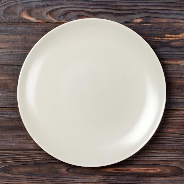 Вид сверху с пустым для вас дизайном, пустая белая тарелка на деревянном Premium Фотографии