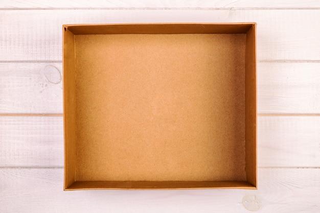 木製、ビンテージ、トーンのトップビューに茶色の空の段ボール箱を開けた Premium写真