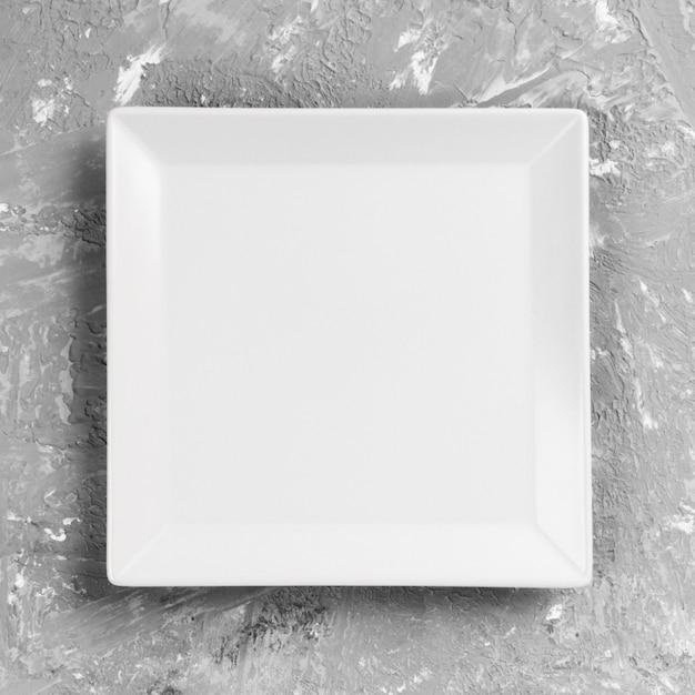 Белая квадратная пластина на сером столе. перспективный вид Premium Фотографии