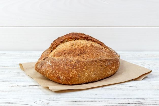 Свежий хлеб на деревянный стол. хлеб на бумажном пакете Premium Фотографии