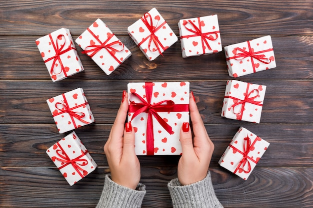 女性の手は、ラップされたバレンタインや赤いリボンと紙で他の休日の手作りプレゼントを与えます。プレゼントボックス、木製のテーブル、デザインのコピースペースと平面図上のギフトの赤いハートの装飾 Premium写真