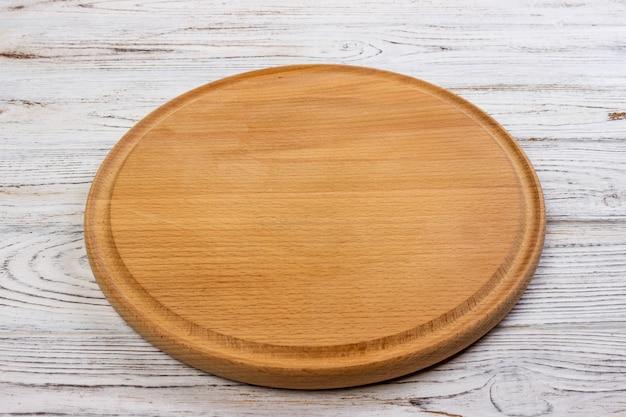 ピザの木製の丸い空のボード Premium写真