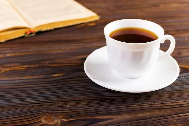 古い本と木製の背景にコーヒーのカップ、トーンのイメージ Premium写真