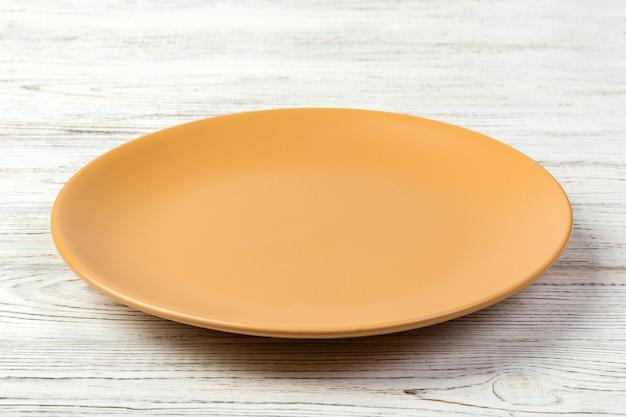 Перспективный вид. пустое оранжевое матовое блюдо на ужин на белом деревянном Premium Фотографии
