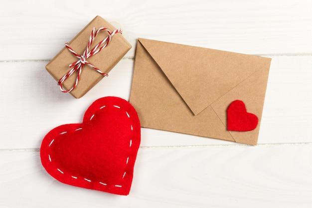赤いハートと白い木製の背景上のギフトボックスと封筒メール Premium写真