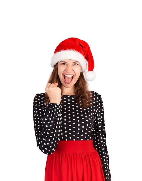 うん、やった。勝利を祝って、勝利に驚くドレスの女性の肖像画。分離されたサンタクロースクリスマス帽子で感情的な女の子 Premium写真