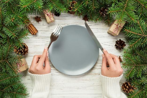 Девушка взгляд сверху держит вилку и нож в руке и готова съесть. керамическая пустая плита круглая на деревянном столе. концепция праздничного ужина с рождественским декором Premium Фотографии