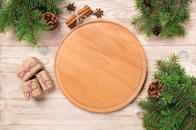 クリスマスの装飾、ラウンドボードとテーブルの背景にピザまな板。新年 Premium写真