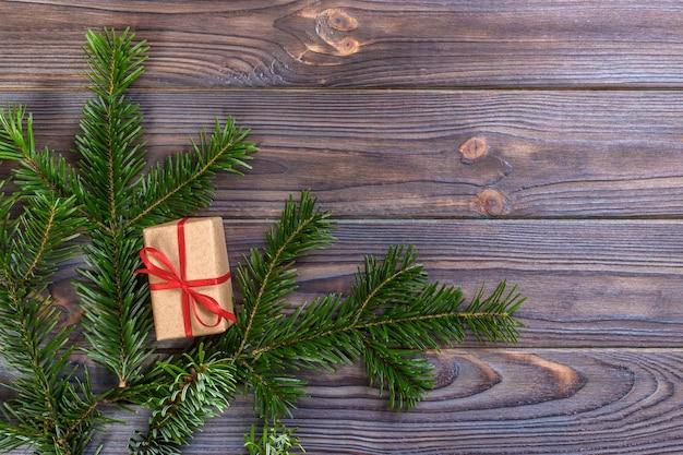 暗い素朴な木製のテーブルのモミの枝にクリスマスプレゼントを包んだ、 Premium写真