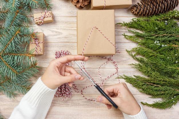 新年の贈り物、贈り物の包装プロセス、裁縫、創造性を包む少女の手 Premium写真