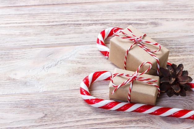 クリスマスキャンデー杖の近くの赤い弓と自家製ボックス Premium写真