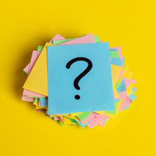 Просто много вопросительных знаков на цветной бумаге Premium Фотографии