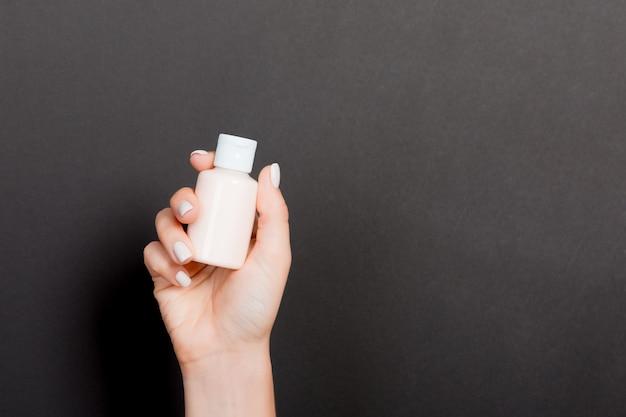ローションのクリームボトルを持っている女性の手 Premium写真