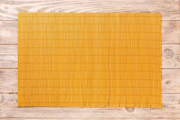Желтый бамбуковый коврик на деревянном фоне Premium Фотографии