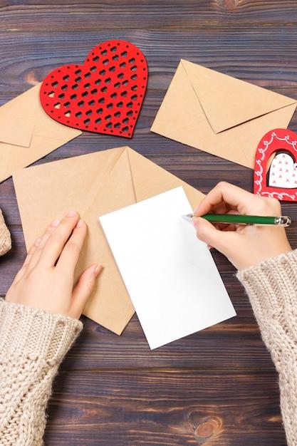 バレンタインデーのためのラブレターやロマンチックな詩を書く女 Premium写真