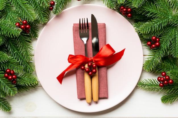 木製の背景にモミの木で飾られたプレートと食器の休日組成 Premium写真