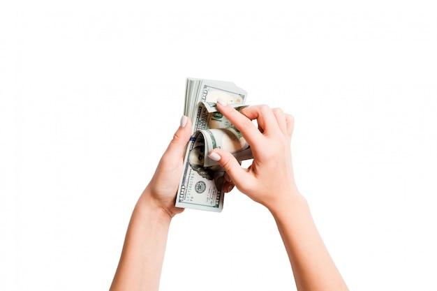 女性の手でお金の束の平面図。分離された白のドルを数えるイメージ Premium写真