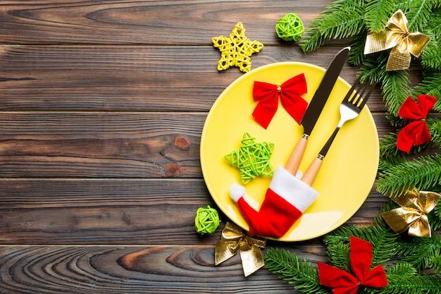 Взгляд сверху вилки, ножа и плиты окруженных с елью и украшениями рождества на деревянной предпосылке. Premium Фотографии