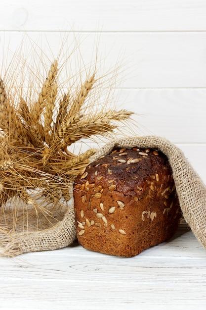 Хлеб с семенами и колосья пшеницы на деревянный стол Premium Фотографии