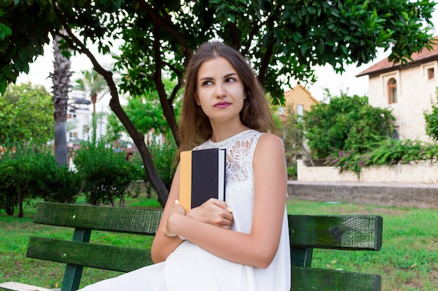 若い女性は本を持っていると外の何かについて夢を見ています Premium写真