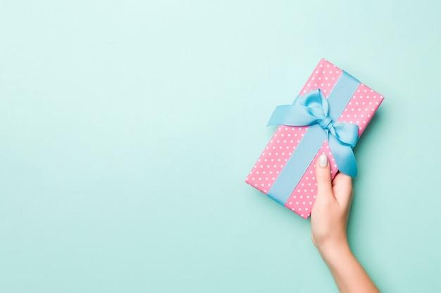 女性の手は、色とりどりの紙に包まれたクリスマスや他の休日の手作りプレゼントを与えます。プレゼントボックス、青いテーブル、コピースペースと平面図上のギフトの装飾 Premium写真