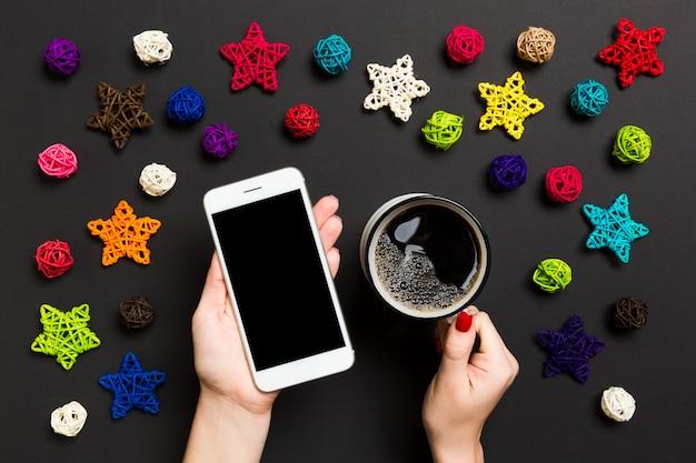 片方の手で携帯電話と黒のもう一方の手でコーヒーカップを保持している女性の平面図です。 Premium写真