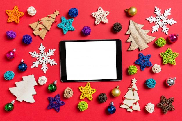 休日の装飾やおもちゃで作られた赤のデジタルタブレットのトップビュー Premium写真
