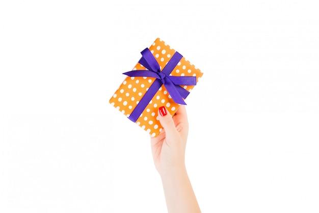 女性の手は、紫色のリボンとオレンジ色の紙で包まれたクリスマスや他の休日の手作りプレゼントを与えます。 Premium写真