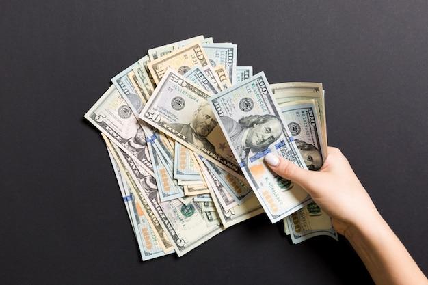 Вид сверху руки бизнес-леди, считая сто и разных долларовых банкнот Premium Фотографии