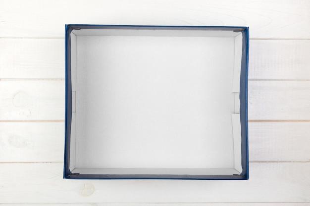 白い木製の背景の机の上に空の白いボックス Premium写真