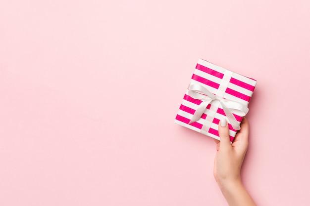 生きているサンゴの色のリボンとストライプのギフトボックスを保持している女性の手。 Premium写真