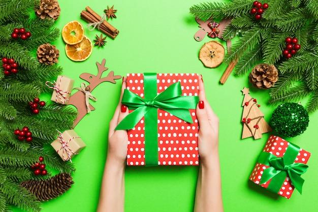 お祝いの緑のクリスマスプレゼントを保持しているトップビュー女性手。モミの木と休日の装飾。休日 Premium写真