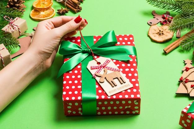 お祝いの緑のクリスマスプレゼントを保持しているトップビュー女性手。モミの木と休日の装飾。年末年始 Premium写真
