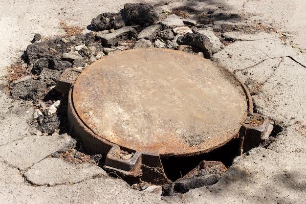Сломанный металлический канализационный люк посреди асфальтированной дороги Premium Фотографии